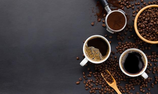 Tasse kaffee und bohne auf schwarzem holztischhintergrund. draufsicht