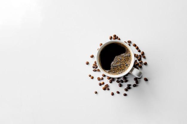 Tasse kaffee und bohne auf weißem tischhintergrund. draufsicht