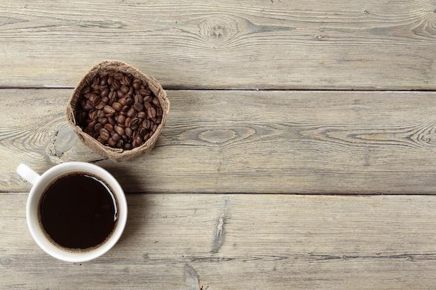Tasse kaffee und bohnen auf hölzernem