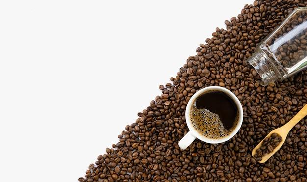 Tasse kaffee und bohnen auf weißem tischhintergrund. draufsicht