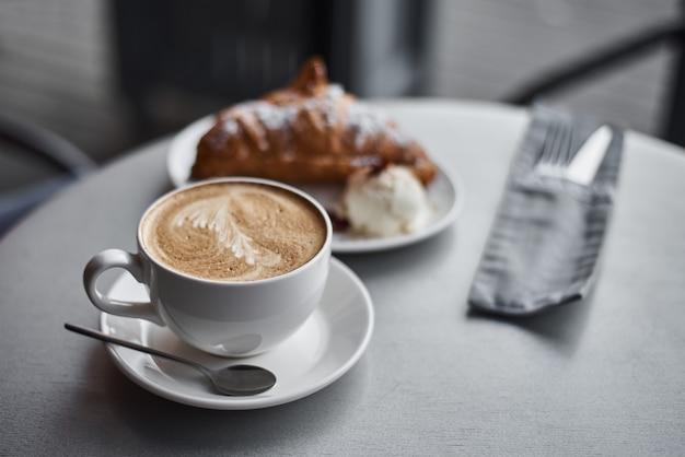 Tasse kaffee und croissant auf dem tisch