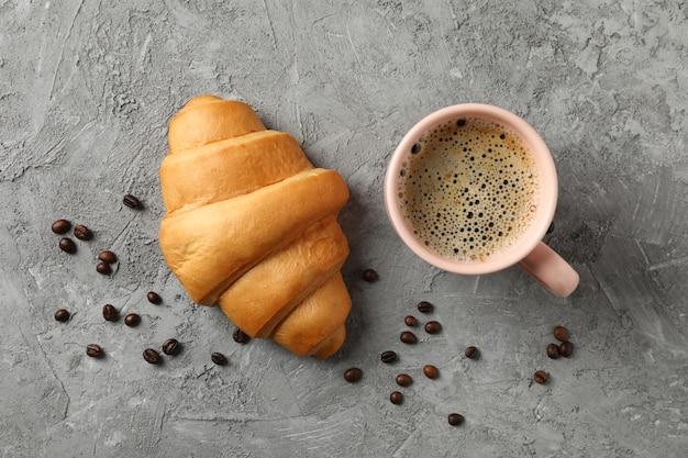 Tasse kaffee und croissant auf grauem hintergrund, draufsicht