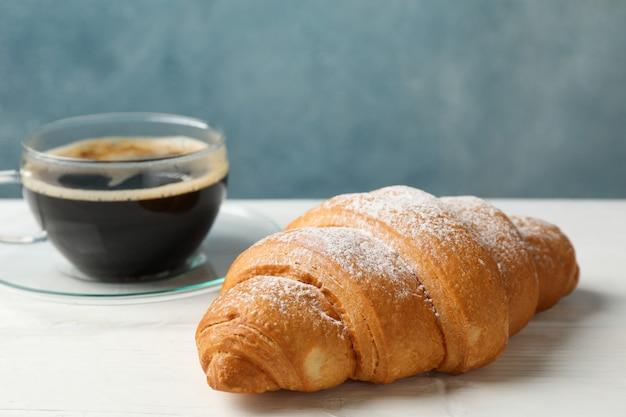 Tasse kaffee und croissant auf holztisch, platz für text