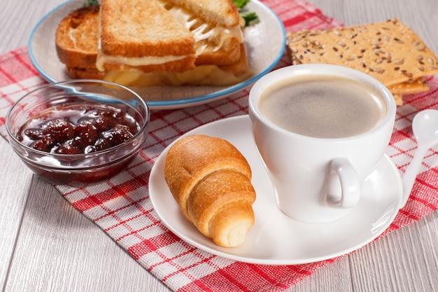 Tasse kaffee und croissant auf untertasse glasschale mit erdbeermarmelade kekse