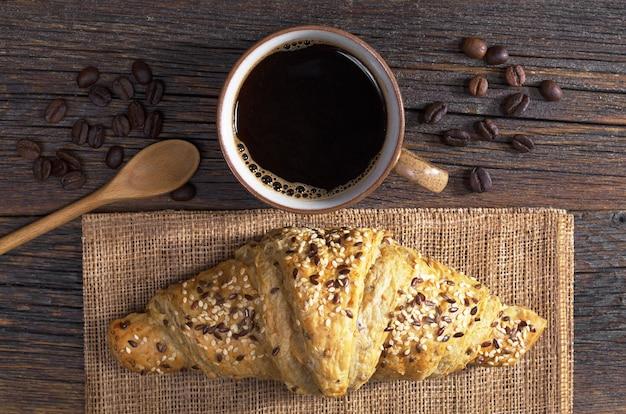 Tasse kaffee und croissant mit sesam zum frühstück auf altem holztisch, ansicht von oben
