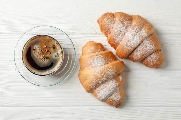 Tasse kaffee und croissants auf hölzernem hintergrund, draufsicht