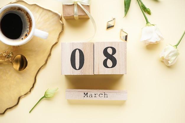 Tasse kaffee und ein hölzerner kalender vom 8. märz mit einer geschenkbox, schönen blumen. internationaler frauentag.