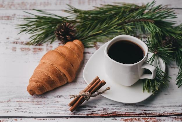 Tasse kaffee und ein hörnchen auf tabelle