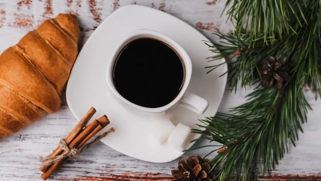 Tasse kaffee und ein hörnchen im dekor des neuen jahres.
