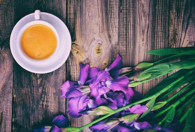 Tasse kaffee und ein strauß blauer iris