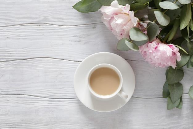 Tasse kaffee und ein strauß rosa pfingstrosen auf einem weißen schreibtisch.