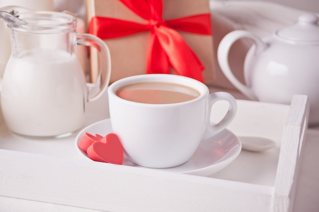 Tasse kaffee und eine herzförmige rote praline mit geschenkbox auf dem weißen tablett