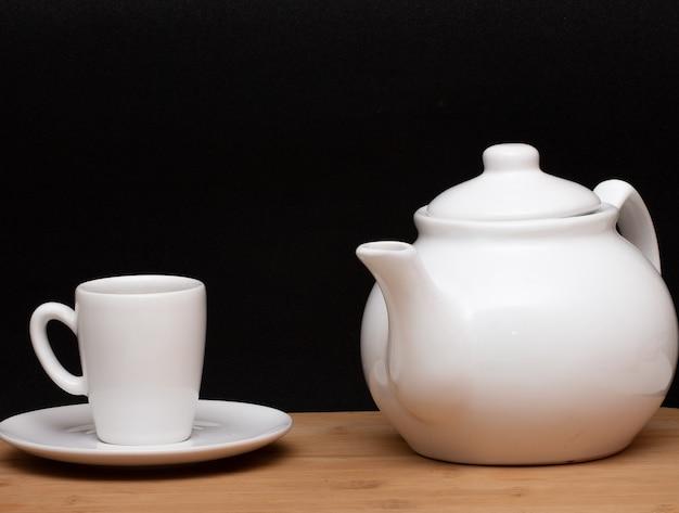 Tasse kaffee und eine kaffeekanne unter dem holztisch