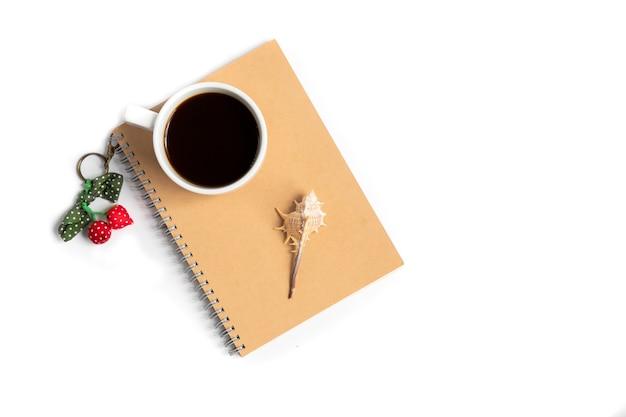 Tasse kaffee und eine muschel auf einem notizbuch