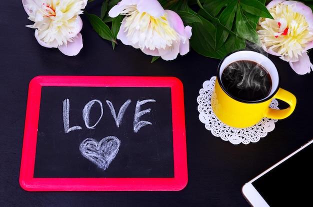 Tasse kaffee und eine schwarze kreidetafel mit liebe