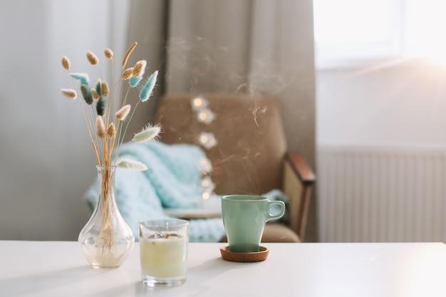 Tasse kaffee und eine transparente vase mit getrockneten blumen am weißen hintergrund