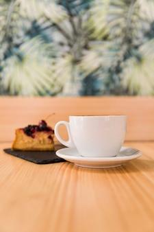 Tasse kaffee und gebäck auf hölzernem schreibtisch