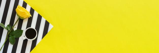 Tasse kaffee und gelbe rose auf stilvoller schwarzweiss-serviette auf gelbem hintergrund. konzept guten morgen oder tag.