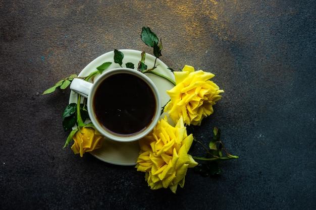 Tasse kaffee und gelbe rosen
