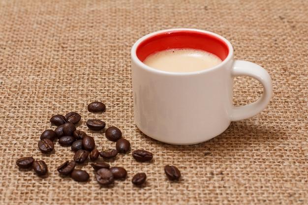 Tasse kaffee und geröstete kaffeebohnen auf sackleinen. ansicht von oben.