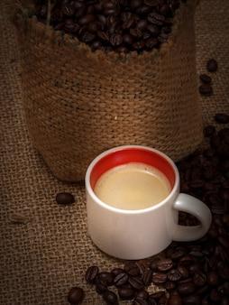 Tasse kaffee und geröstete kaffeebohnen in einem leinensack auf sackleinen