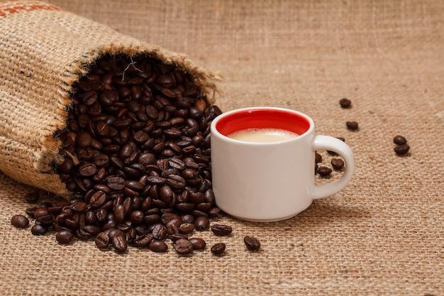 Tasse kaffee und geröstete kaffeebohnen in einem leinwandsack auf sackleinenhintergrund.