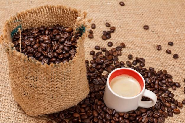 Tasse kaffee und geröstete kaffeebohnen in einem segeltuchsack auf sackleinen. ansicht von oben.