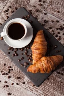 Tasse kaffee und gestreute kaffeebohnen mit frischen croissants. leckeres dessert.