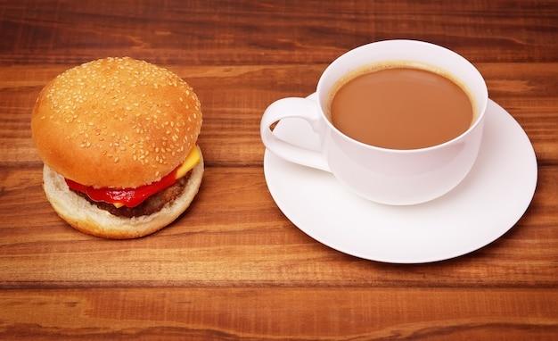 Tasse kaffee und hamburger mit frischen tomaten, salat, käse und schnitzel auf holzhintergrund.