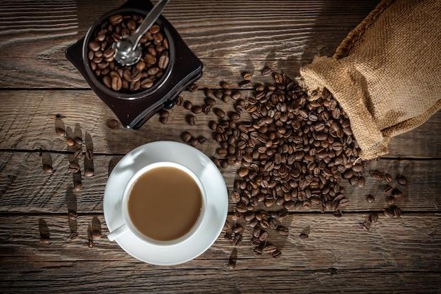 Tasse kaffee und haufen bohnen auf einem holztisch