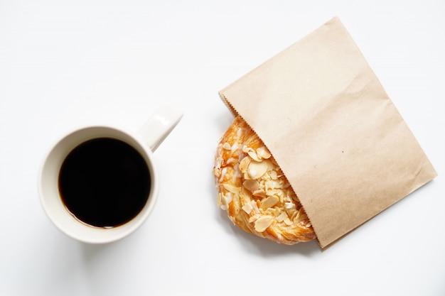 Tasse kaffee und hörnchen mit planungsurlaubsreise und bereiten vor, um zu gehen