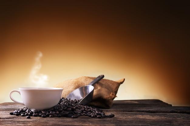 Tasse kaffee und kaffeebohnen auf altem hölzernem hintergrund