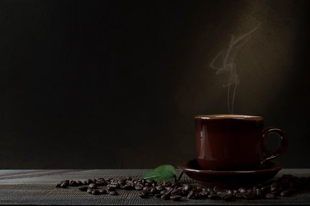 Tasse kaffee und kaffeebohnen auf dem tisch. dunkler hintergrund.