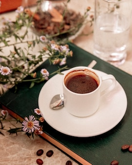 Tasse kaffee und kaffeebohnen auf dem tisch