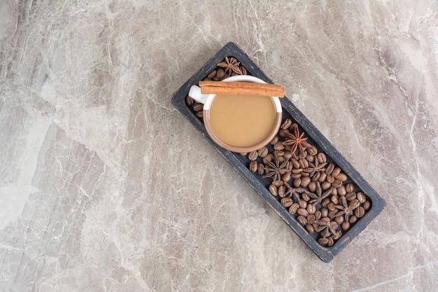 Tasse kaffee und kaffeebohnen auf dunklem teller.