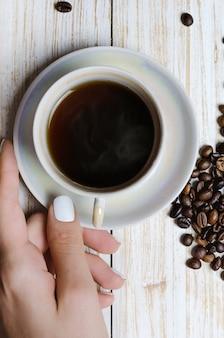 Tasse kaffee und kaffeebohnen auf hölzernem brett.