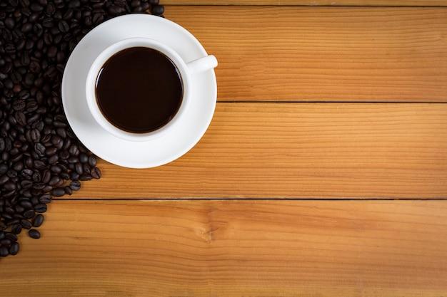 Tasse kaffee und kaffeebohnen auf holz