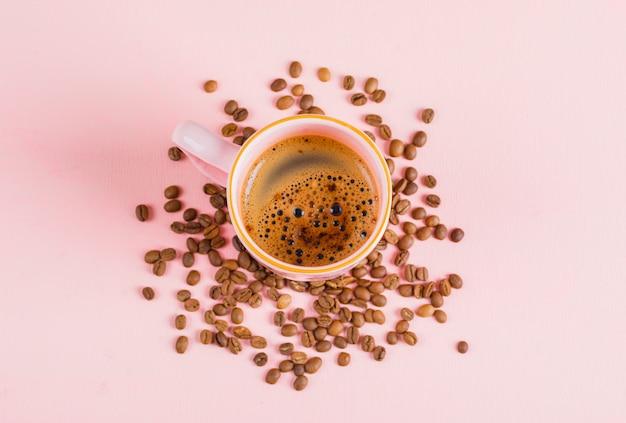 Tasse kaffee und kaffeebohnen auf rosa oberfläche