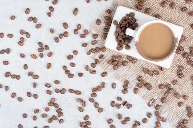 Tasse kaffee und kaffeebohnen auf sackleinen. foto in hoher qualität
