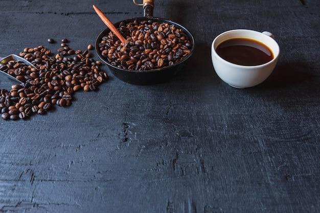 Tasse kaffee und kaffeebohnen auf schwarzem hintergrund