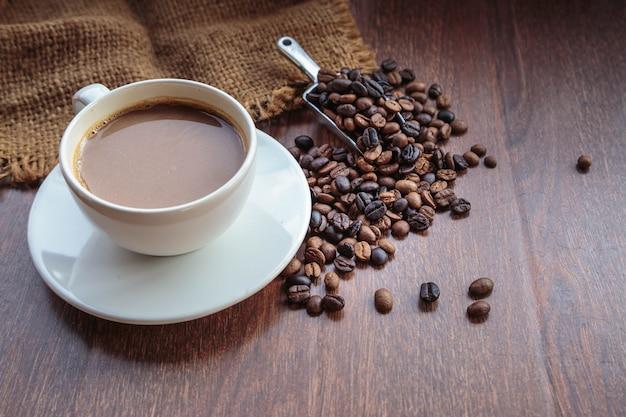 Tasse kaffee und kaffeebohnen in einem sack, ansicht von oben