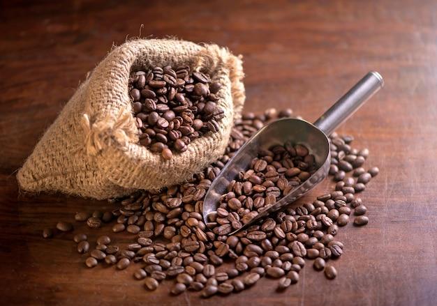 Tasse kaffee und kaffeebohnen in einem sack auf dunklem hintergrund, draufsicht