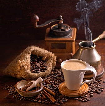 Tasse kaffee und kaffeebohnen in einem sack auf dunklem tisch, draufsicht