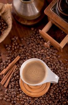 Tasse kaffee und kaffeebohnen in einem sack auf dunkler oberfläche, draufsicht