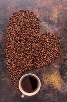 Tasse kaffee und kaffeebohnen in form eines herzens gegossen