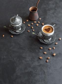Tasse kaffee und kaffeebohnen mit gemahlenem pulver auf schwarzem hintergrund, draufsicht.