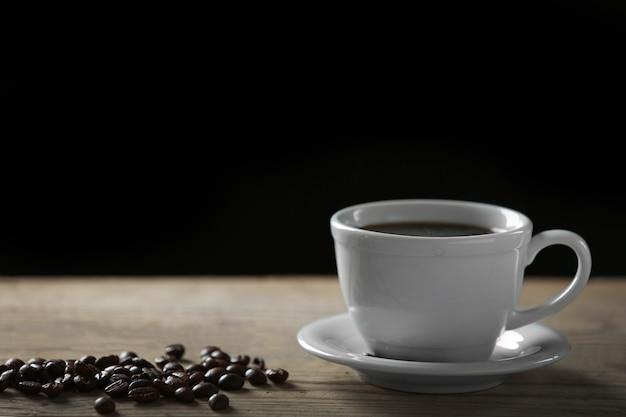Tasse kaffee und kaffeekörner auf holztisch, auf grauer oberfläche