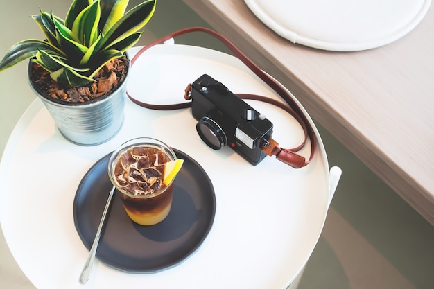 Tasse kaffee und kamera auf dem tisch im café