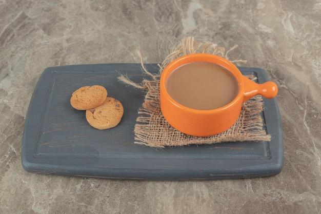Tasse kaffee und kekse auf dunklem teller