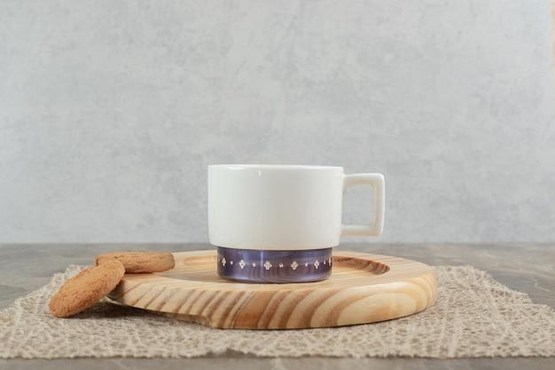 Tasse kaffee und kekse auf holzteller